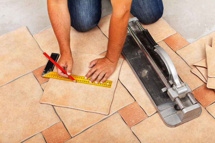 Man making measurements of light tan and tan ceramic floor tiles while kneeling down on the floor.