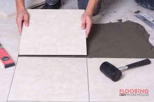 A Tiler That Has a Tile In His Hands That He is Installing